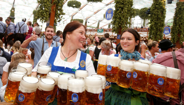 Image: Waitresses carry mugs of beer during the opening day of the 184th Oktoberfest in Munich