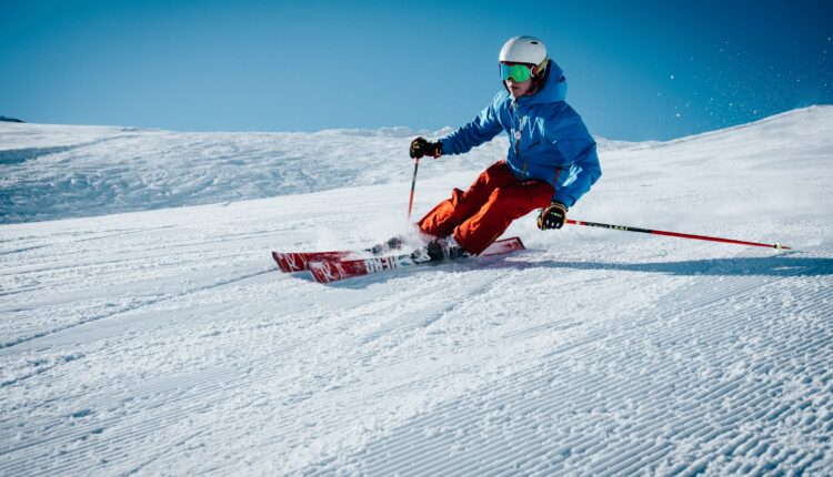 man ice skiing on hill